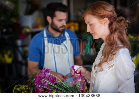 Woman spraying water on bunch of flowers while man preparing flower bouquet in the flower shop