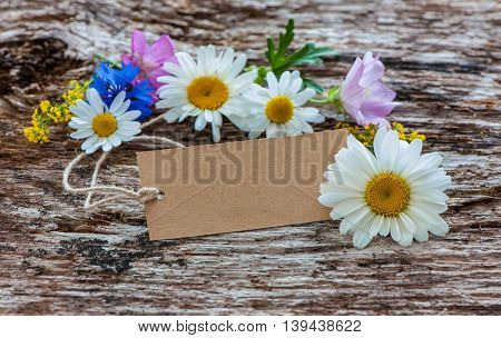 Wild Flowers with a vintage tag on wooden background