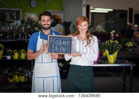 Couple holding slate with flower shop sign in the flower shop