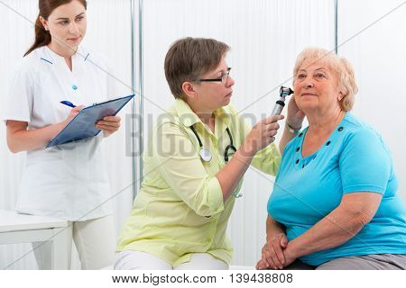Ear examination. ENT physician looking into patient's ear with an instrument