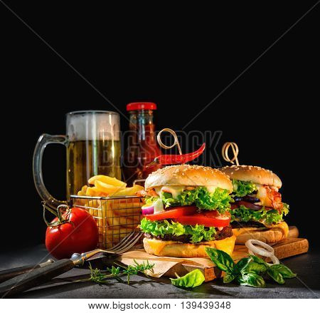 Delicious hamburgers with french fries and beer on dark background