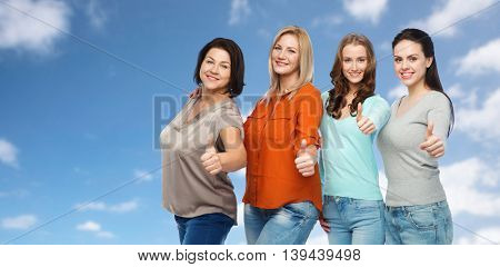 friendship, fashion, body positive, gesture and people concept - group of happy different size women in casual clothes showing thumbs up over blue sky and clouds background