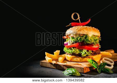 Delicious hamburgers with french fries on dark background