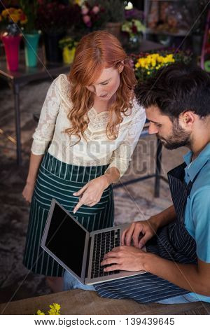 Couple using laptop together in the flower shop