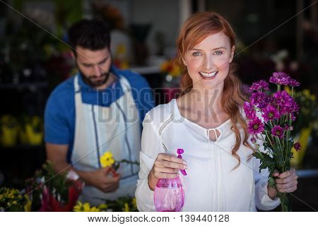 Woman holding bunch of flowers while man preparing flower bouquet in the flower shop