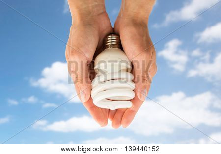 recycling, electricity, environment and ecology concept - close up of hands holding energy saving lightbulb or lamp over blue sky and clouds background