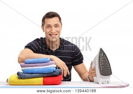 Happy young guy sitting behind an ironing board with a pile of clothes isolated on white background
