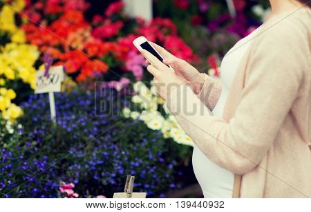 sale, shopping, pregnancy, gardening and people concept - close up of pregnant woman with smartphone at street flower market