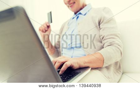 technology, age and people concept - close up of happy senior woman with laptop compute and credit or bank card r at home