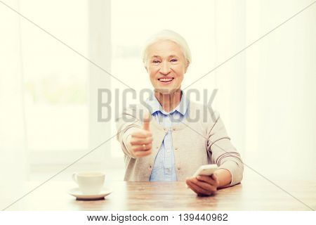 technology, communication, gesture, age and people concept - happy senior woman with smartphone and coffee sitting at table and showing thumbs up at home