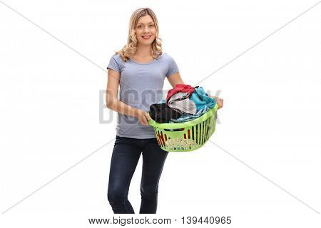 Cheerful woman holding a laundry basket full of clothes isolated on white background