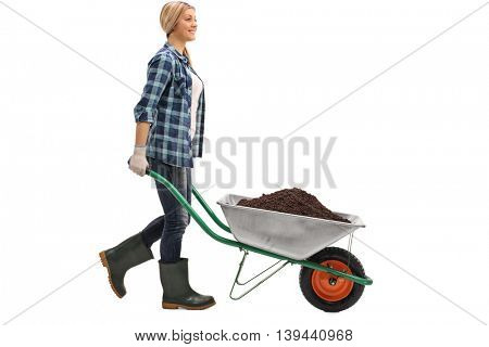 Profile shot of a young cheerful woman pushing a wheelbarrow full of dirt isolated on white background