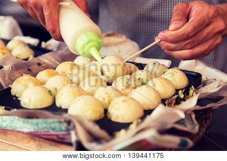 cooking, asian kitchen and food concept - cook stuffing dough or rice balls with sause at street market