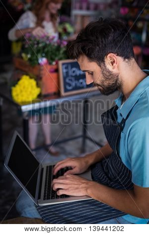 Male florist sitting and using laptop in the flower shop