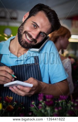 Male florist taking order on mobile phone in the flower shop
