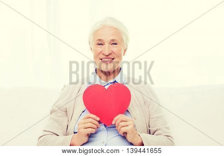 age, holidays, valentines day, love and people concept - happy smiling senior woman with red heart shape at home