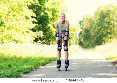 fitness, sport, summer, rollerblading and healthy lifestyle concept - happy young woman in rollerblades and protective gear riding outdoors