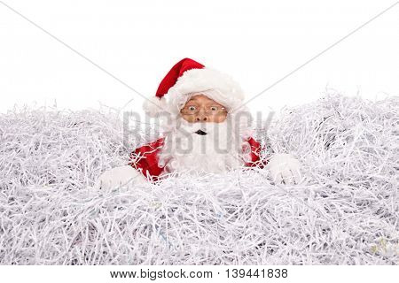 Confused Santa Claus drowning in a pile of shredded paper isolated on white background