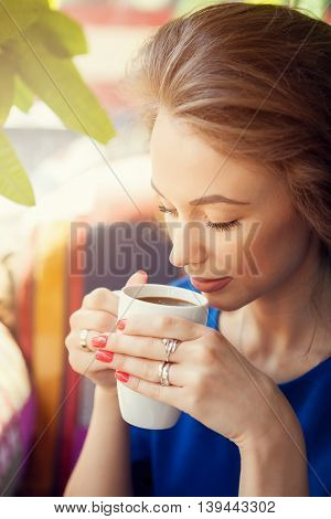 Young Woman Enjoying A Cup Of Coffee In Soft Focus Portrait