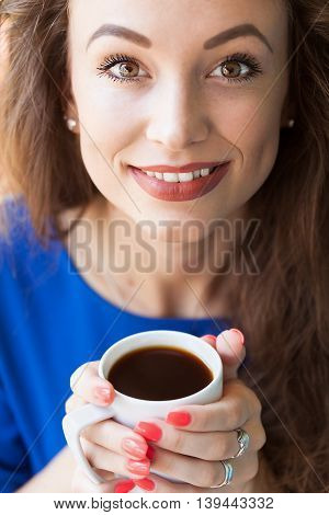 Woman Smiling With A Cup Of Coffee In Hands