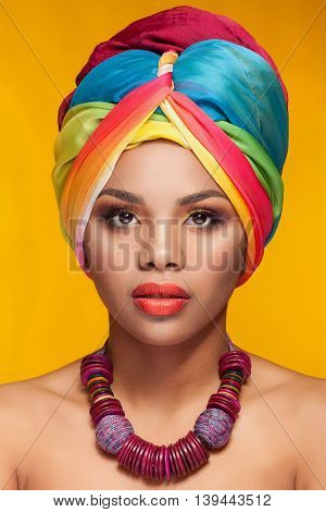 Young woman with afro american turban on yellow background in studio photo. Beauty and make up. Traditions and culture