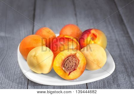 Southern fruit, apricots and nectarines in a plate on a gray-blue wooden background