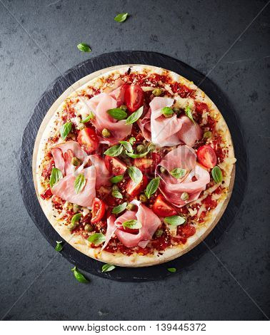 Pizza topped with black forest ham, capers and tomatoes