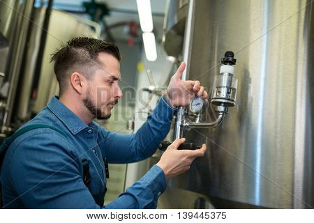 Attentive brewer checking pressure at brewery