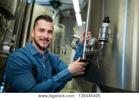 Portrait of happy brewer checking pressure at brewery