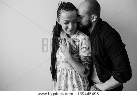 man and woman posing against a white wall