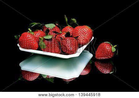 ripe juicy strawberries closeup on a black background. horizontal photo.