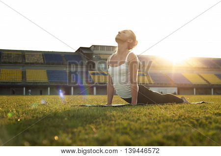 Yong blonde woman doing yoga outdoors. Cobra Pose exercise.