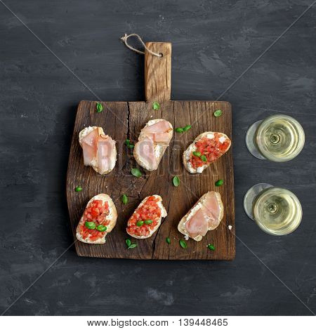 Sandwich with tomatoes goat cheese and ham on a wooden board on a dark surface. Wine with appetizers for wine