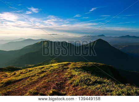 Trail on top of the mountain on the background of sunset sky