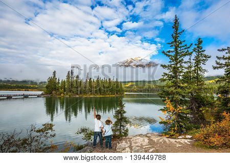 Morning in the Rocky Mountains, Jasper Park. Two boys looking at a lake holding hands. Concept of active vacation and tourism