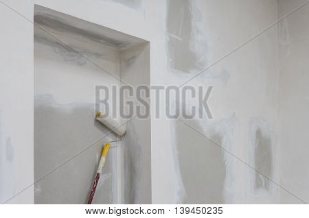 Unfinished wall in apartment and paint roller.jpg