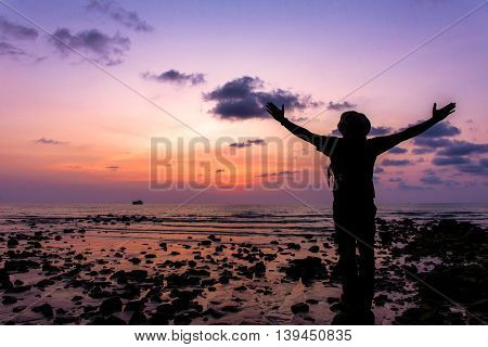 Silhouette Of Traveler With Hands Up In The Sunset On The Ocean