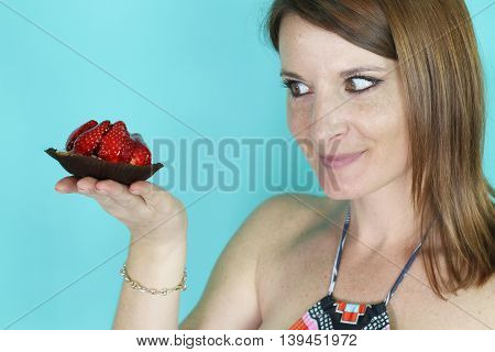 young woman holding a strawberry tart over a blue background