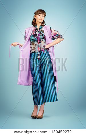 Vogue shot of a female model posing at studio. Fashion collection. Full length portrait.