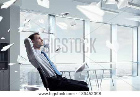 Businessman relaxing in his office .  Mixed media