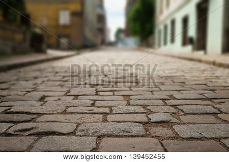 perspective view of old paved road in town, background