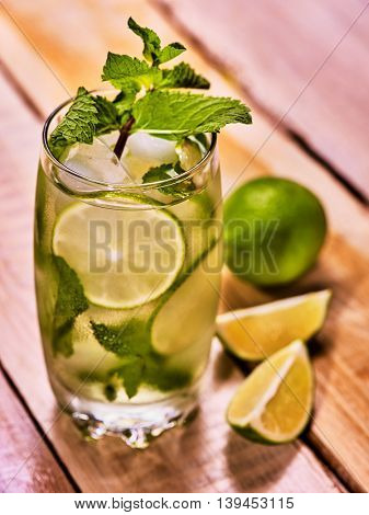On wooden boards glass with alcohol cocktail and ice cubes. Cocktail two hundred forty-two cocktail mohito with slice, quartered lime and mint leaf. Country life. Wooden boards background. Top view.