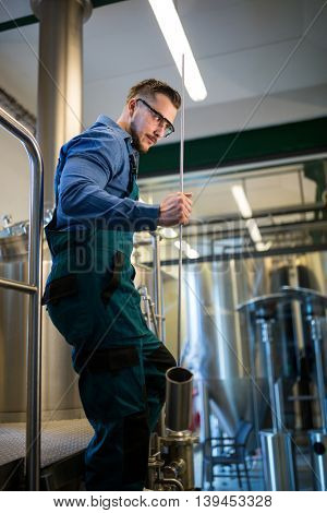 Thoughtful brewer holding working equipment at brewery