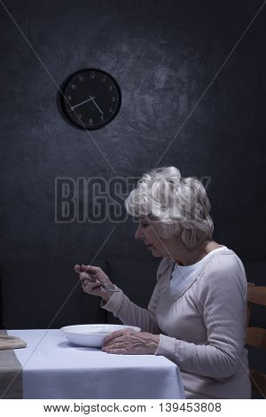 Older sad woman eating dinner alone in the dark room