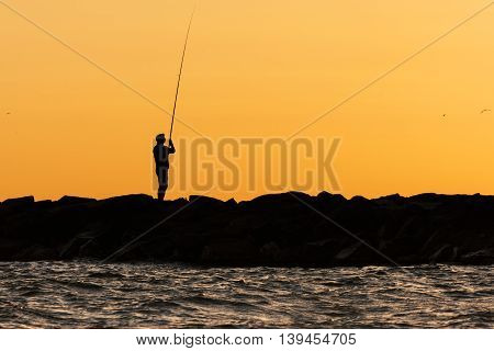 Fishermen silhouette at sunrise. Fisherman at the dusk