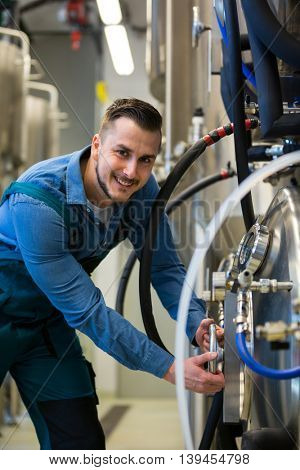 Portrait of happy maintained worker working at brewery