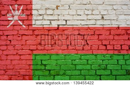 Flag of Oman painted on brick wall background texture