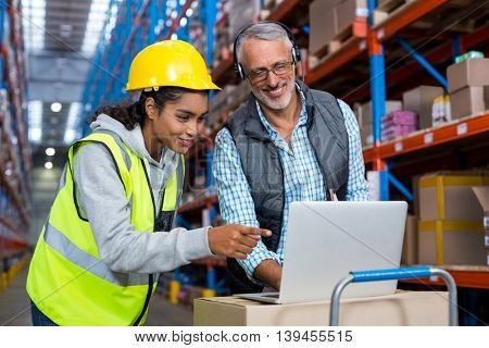 Worker and manager are looking a laptop and smiling in a warehouse