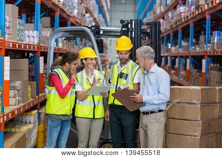 Manager talking with the workers in a warehouse