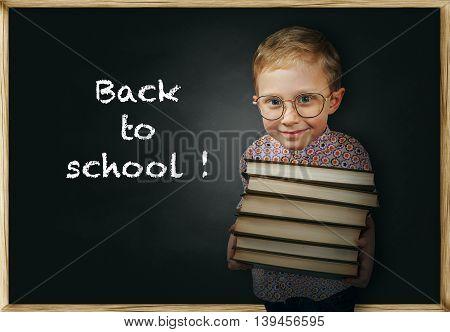 Boy with books near school chalkboard .